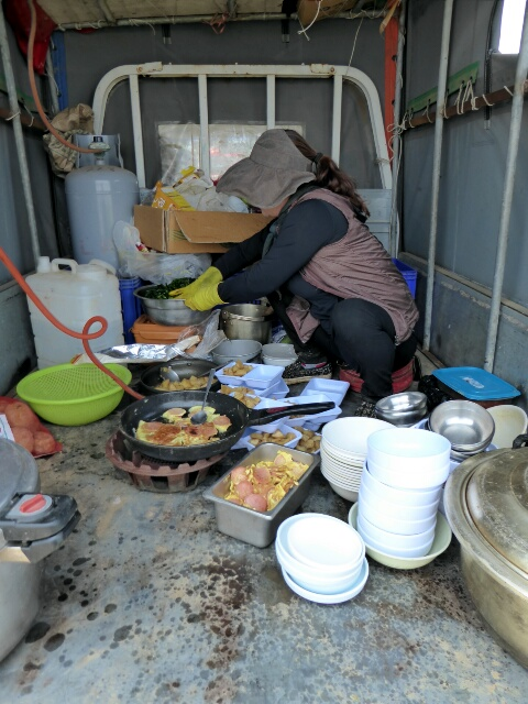 Cooking lunch in the back of a truck for the garlic pickers