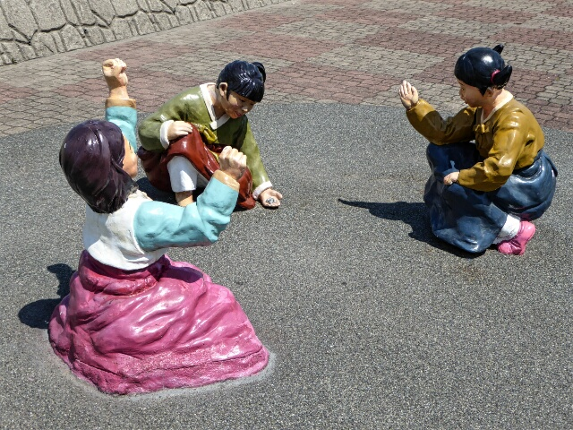Children's game of marbles on the Street of Memories in Dodu
