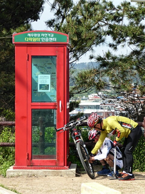 On the round-Jeju bike path, riders get their stamps at old phone booths