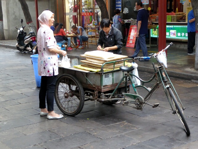 Lady buying tofu from the man with the bike