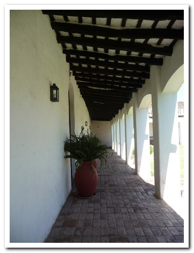 Shaded hallway leading onto the courtyard at Estancia Caroya