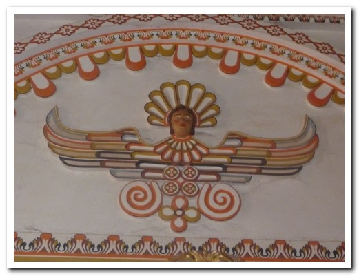 Native with traditional head dress depicted as an angel on the wall of the church